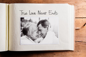 Photo album with black-and-white picture of senior couple in love, hugging and True love never ends sign. Studio shot on wooden background.