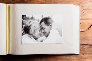 Photo album with black-and-white picture of senior couple in love, hugging. Studio shot on wooden background.