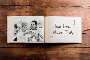 Photo album with black-and-white picture of senior couple on vacation. Studio shot on wooden background.