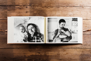 Photo album with pictures of young father and his cute newborn baby son. Fathers day concept. Studio shot on woden background.