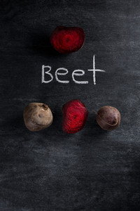 Photo of a cut beet over dark chalkboard background