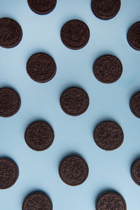 Photo of a lot of colorful chocolate cookies over blue table background.