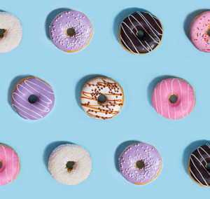 Photo of a lot of colorful sweeties donuts over blue table background.