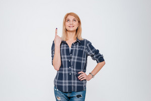 Photo of a smiling woman pointing isolated on a white background. Looking aside.