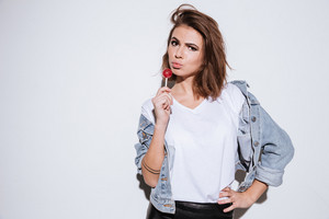 Photo of a young pretty woman dressed in jeans jacket standing isolated over white background while holding candy.