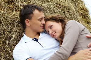 Photo of affectionate couple having rest on haystack