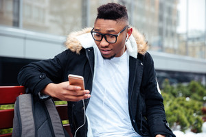 Photo of african man holding his cellphone in hands and chatting while listen to music outdoors.