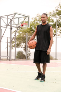 Photo of african smiling basketball player standing in the street with basketball hoop at background. Looking at camera.