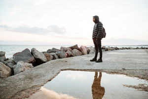 Photo of african young man dressed in warm clothes walking on the beach. Looking aside.