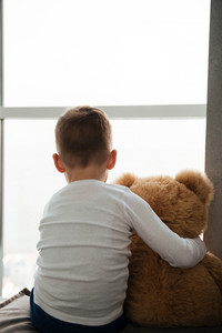 Photo of alone little boy sitting with teddy bear near window and waiting for parents at home. Look at window.