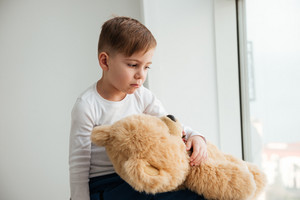 Photo of alone sad little boy near window with teddy bear waiting for parents at home. Look aside.