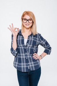 Photo of an attractive woman wearing eyeglasses posing isolated on a white background and make okay gesture. Looking at camera.