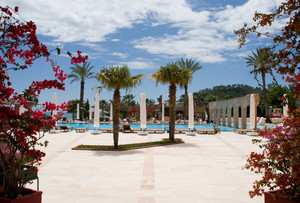 Photo of area with palms and swimming pool with tourists near by