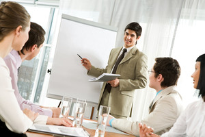 Photo of attentive business partners looking at successful entrepreneur pointing at whiteboard in office