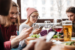 Photo of attractive friends sitting in cafe and drinking alcohol while using mobile phones.