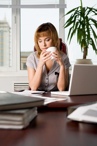 Photo of attractive woman sitting at workplace in the office and drinking tea