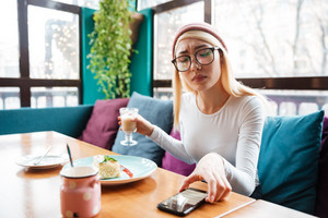 Photo of attractive young lady wearing hat and glasses using cellphone while sitting in cafe.