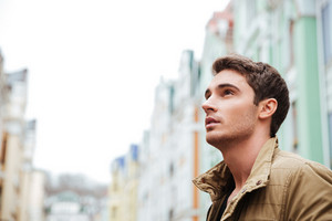 Photo of attractive young man walking on the street and looking aside.