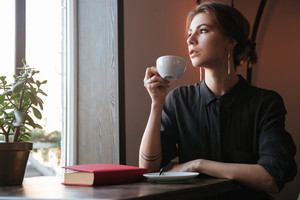 Photo of attractive young woman sitting at the table near book in cafe and looking aside while drinking coffee.