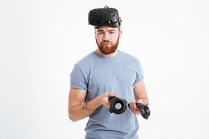 Photo of bearded confused man wearing virtual reality device standing over white background with joysticks. Look at camera.