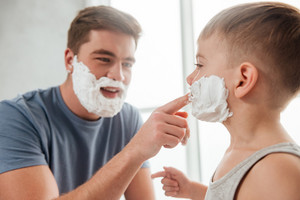 Photo of bearded father and son are applying shaving foam on their faces and smiling while shaving in bathroom