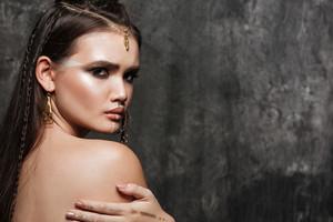 Photo of beautiful asian model with bright makeup and sunburn skin. Look at camera.