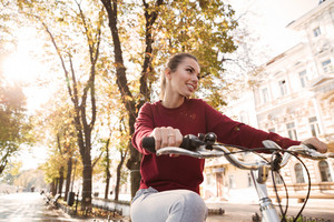 Photo of beautiful caucasian lady dressed in sweater walking with her bicycle outdoors. Look aside.