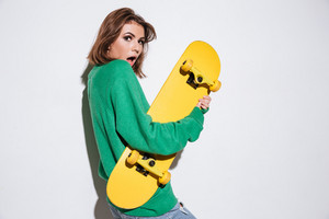 Photo of beautiful confused skater lady dressed in green sweater standing isolated over white background with skateboard.