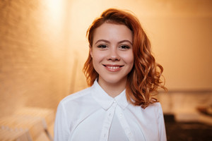Photo of beautiful redhead young woman dressed in white shirt looking at camera.