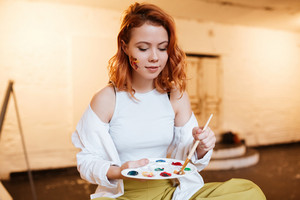 Photo of beautiful young redhead lady painter with oil paints on face in artist workshop. Look at palette.