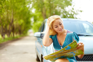 Photo of blond woman sitting by her car and looking at map