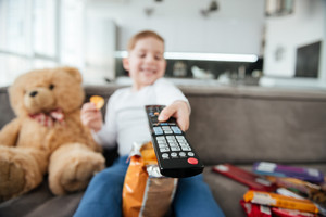 Photo of boy sitting on sofa with teddy bear at home and watching TV while eating chips. Holding remote control. Focus on remote control.