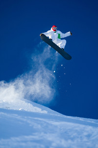 Photo of brave sportsman jumping on snowboard over blue sky
