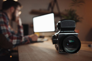 Photo of camera standing on table near bearded web designer dressed in shirt in a cage print and wearing glasses . Focus on camera.