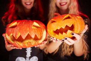 Photo of carved Halloween pumpkins on female palms