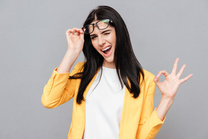 Photo of charming young woman wearing eyeglasses and dressed in yellow jacket make Okay gesture over grey background. Look at camera.