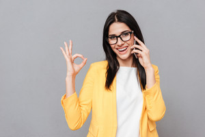 Photo of charming young woman wearing eyeglasses make Okay gesture while talking by her phone over grey background. Look at camera.
