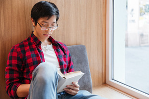 Photo of cheerful asian student reading a book in university library sitting on sofa.