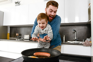 Photo of cheerful bearded father dressed in blue sweater cooking at kitchen with his little cute son