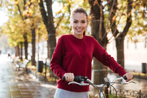 Photo of cheerful caucasian lady dressed in sweater walking with her bicycle outdoors. Look at camera.