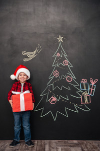 Photo of cheerful child wearing hat holding a big gift near Christmas tree drawing on blackboard. Looking at camera.
