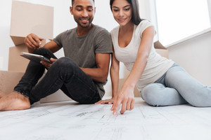 Photo of cheerful couple planning decoration at new home sitting on the floor. Housewarming.