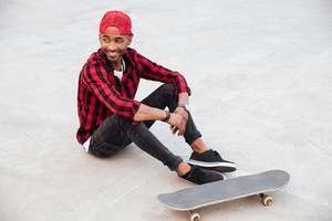Photo of cheerful dark skinned boy wearing cap sitting near his skateboard. Against nature background.