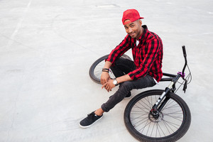 Photo of cheerful dark skinned guy wearing cap sitting on his bicycle. Against nature background. Looking at the camera.