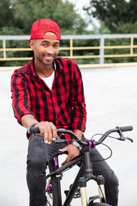 Photo of cheerful dark skinned man wearing cap sitting on his bicycle. Against nature background. Looking at the camera.