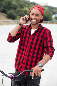 Photo of cheerful dark skinned man wearing cap sitting on his bicycle. Against nature background. Talking on his phone.