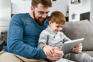 Photo of cheerful family using tablet computer indoors. Look at tablet computer.