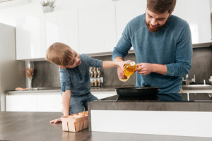 Photo of cheerful father dressed in blue sweater cooking at kitchen with his little cute son