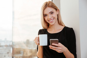 Photo of cheerful lady worker standing in office holding cup of coffee while chatting by her phone. Look at camera.