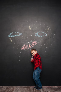 Photo of cheerful little kid looking at camera while holding umbrella on the chalkboard with drawings of a rain.